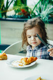 Cute little girl having breakfast with the croissant in a restaurant. Royalty Free Stock Photography