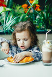 Cute little girl having breakfast with the croissant in a restaurant. Royalty Free Stock Images