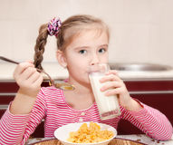 Cute little girl having breakfast drinking milk Stock Image