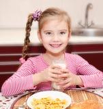 Cute little girl having breakfast drinking milk Royalty Free Stock Photo