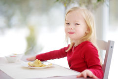Cute little girl having crepes for breakfast. At sunny kitchen Stock Photos