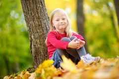 Cute little girl having fun on beautiful autumn day. Happy child playing in autumn park. Kid gathering yellow fall foliage. Stock Photos