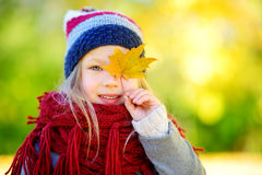 Cute little girl having fun on beautiful autumn day. Happy child playing in autumn park. Kid gathering yellow fall foliage. Royalty Free Stock Images