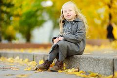 Cute little girl having fun on beautiful autumn day. Happy child playing in autumn park. Kid gathering yellow fall foliage. stock photography