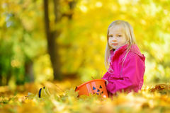 Cute little girl having fun on beautiful autumn day. Happy child playing in autumn park. Kid gathering yellow fall foliage. Autumn activities for children Royalty Free Stock Photo