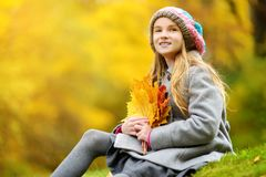 Cute little girl having fun on beautiful autumn day. Happy child playing in autumn park. Kid gathering yellow fall foliage. royalty free stock photos