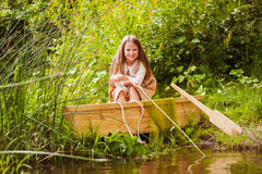 Cute little girl having fun in a boat by a river Stock Photos