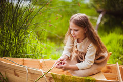 Cute little girl having fun in a boat by a river Stock Images
