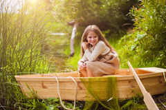 Cute little girl having fun in a boat by a river Stock Photography