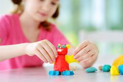 Cute little girl having fun with colorful modeling clay at a daycare Royalty Free Stock Images
