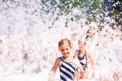 Cute little girl having fun at foam party. Stock Photography