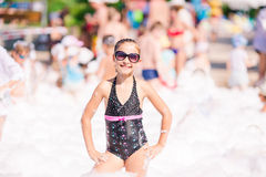 Cute little girl having fun at foam party. Stock Images
