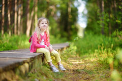 Cute little girl having fun during forest hike on beautiful summer day Stock Images