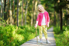 Cute little girl having fun during forest hike on beautiful summer day Stock Photos
