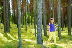 Cute little girl having fun during forest hike on beautiful summer day stock photo