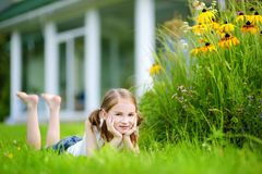 Cute little girl having fun on a grass in her back yard Royalty Free Stock Image