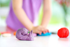 Cute little girl having fun with modeling clay at a daycare. Creative kid molding at home. Royalty Free Stock Photography