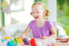 Cute little girl having fun with modeling clay at a daycare. Creative kid molding at home. Royalty Free Stock Photos