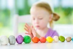 Cute little girl having fun with modeling clay at a daycare. Creative kid molding at home. Royalty Free Stock Images