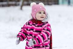 Cute little girl having fun outdoor on nature at winter. Stock Photos