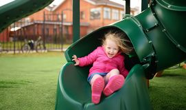 Cute little girl having fun on outdoor playground stock image