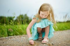 Cute little girl having fun outdoors on sunny summer evening. Child exploring nature. Summer activities for kids royalty free stock image