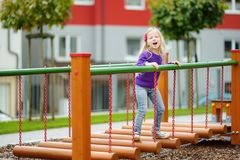 Cute little girl having fun on a playground outdoors in summer. Royalty Free Stock Photography