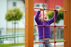 Cute little girl having fun on a playground outdoors in summer. Stock Photography