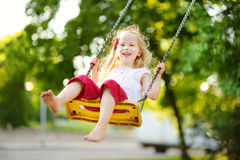 Cute little girl having fun on a playground outdoors on warm summer day. Cute kid swinging outdoors. Summer outdoor leisure for kids Stock Photo