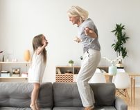 Cute little girl playing with grandmother jumping on couch toget stock photos