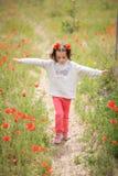 Cute little girl having fun in a poppy field Royalty Free Stock Photography