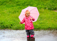 Cute little girl having fun on rain Stock Image
