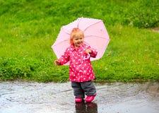 Cute little girl having fun on rain Stock Image