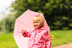 Cute little girl having fun on rain. Kids play outdoors royalty free stock images