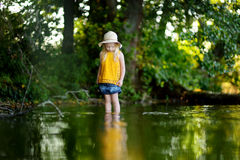 Cute little girl having fun by a river on sunny summer day Royalty Free Stock Photo