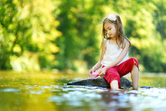 Cute little girl having fun by a river on warm summer day Stock Photos