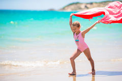 Cute little girl having fun running with towel on royalty free stock image