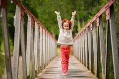 Cute little girl having fun in a rural bridge Stock Photos