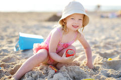 Cute little girl having fun with the sand. On a beautiful evening beach royalty free stock photos