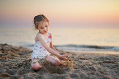 Cute little girl having fun with the sand on a evening beach Royalty Free Stock Photos