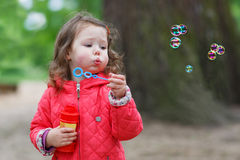 Cute little girl having fun with soap bubbles Royalty Free Stock Image