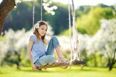 Cute little girl having fun on a swing in blossoming old apple tree garden outdoors on sunny spring day. stock images