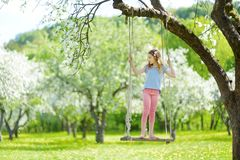Cute little girl having fun on a swing in blossoming old apple tree garden outdoors on sunny spring day royalty free stock photos