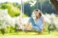 Cute little girl having fun on a swing in blossoming old apple tree garden outdoors on sunny spring day stock images