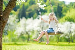 Cute little girl having fun on a swing in blossoming old apple tree garden outdoors on sunny spring day stock photos