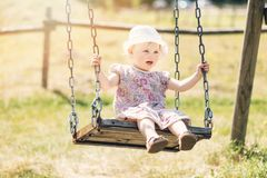 Cute little girl having fun on a swing Royalty Free Stock Images