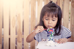Cute little girl having fun to paint on stucco do Royalty Free Stock Image
