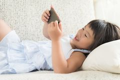 Cute little girl having fun to play game on smart phone stock images