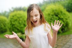 Cute little girl having fun under warm summer rain. Child playing outdoors royalty free stock photography