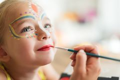 Cute little girl having her face painted for Halloween party. Halloween or carnival family lifestyle background. Face painting. Cute little girl having her face royalty free stock images